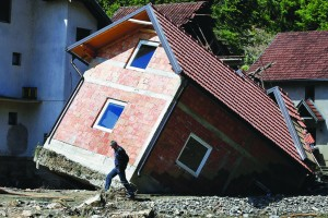 A man walks past a house that was uprooted by floods in the village of Krupanj, Serbia. (Reuters)