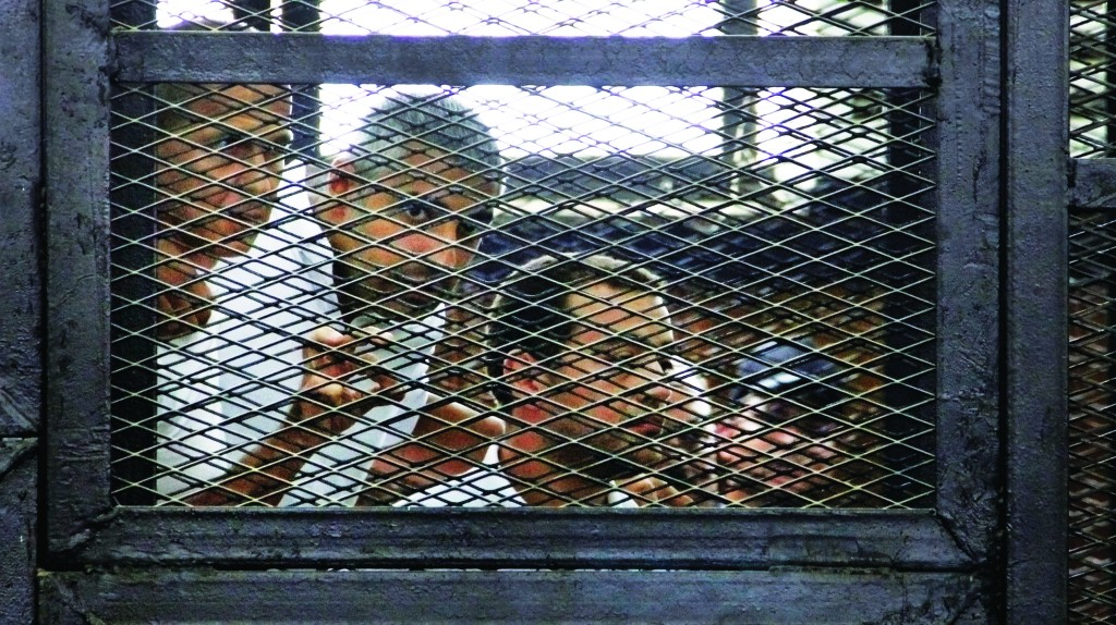 El Shorouk Newspaper From left, Australian correspondent Peter Greste, Canadian-Egyptian acting bureau chief of al-Jazeera Mohamed Fahmy, and Egyptian producer Baher Mohammed appear in a defendant's cage in a courtroom in Cairo, Egypt, Monday. (AP Photo/Heba Elkholy, )