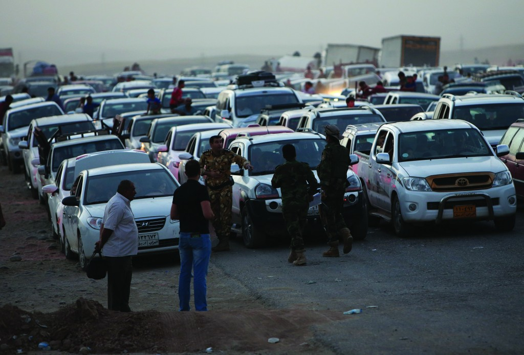Fleeing Iraqi citizens from Mosul and other northern towns, wait in a long traffic queue at a Kurdish security forces checkpoint, at a highway between the Iraqi city of Mosul and the Kurdish city of Irbil, in the Khazer area northern Iraq, Wednesday.  (AP Photo/Hussein Malla)