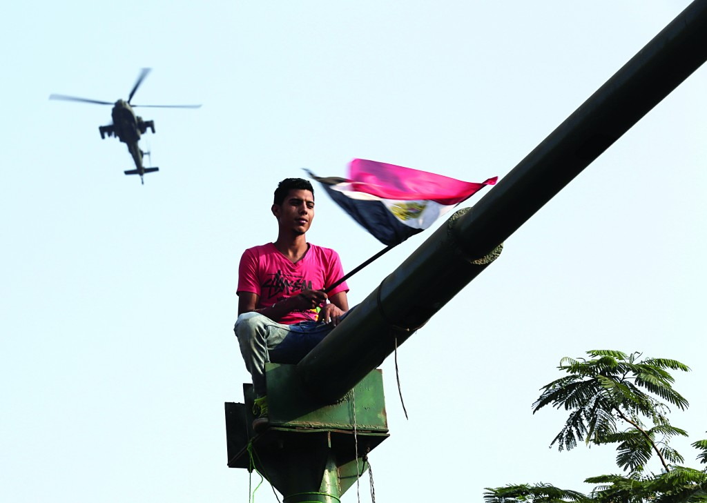 A supporter of Egyptian President Abdel-Fattah el-Sissi celebrates his inauguration from atop a street post as an army helicopter flies over Tahrir Square in Cairo, Egypt, Sunday, Sunday. (AP Photo/Thomas Hartwell)