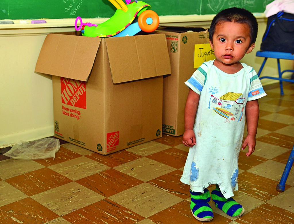 A one-year-old stands in the clothes he arrived in from El Salvador Friday, at a religious charity organization in Brownsville, Texas.  (AP Photo/The Brownsville Herald, Miguel Roberts)