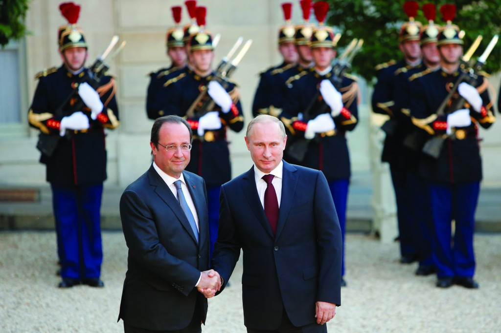 French President Francois Hollande (L) welcomes Russian President Vladimir Putin on his arrival at the Elysee Palace in Paris, Thursday. (AP Photo/Francois Mori)