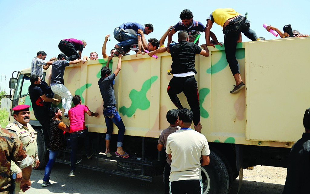 Iraqi men board a military truck to join the Iraqi army at the main recruiting center in Baghdad, Iraq, after authorities urged Iraqis to help battle insurgents. (AP Photo/Karim Kadim)