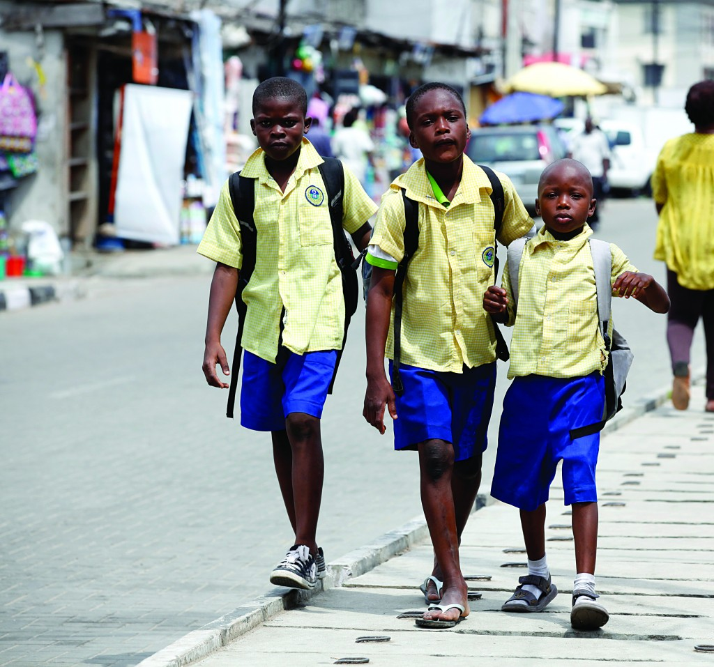 School children walk in the street in the Obalende area of Lagos, Nigeria.  About 30 million primary school-aged children in sub-Saharan Africa are not in class, partially because of conflict and poverty, and progress to get them back to school has stalled, two U.N. agencies said. (AP Photo/Sunday Alamba)