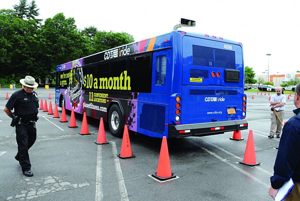 Obstacle Course: A police officer on Wednesday watches a bus driver back up between safety cones during the Capital District Transportation Authorities' annual Bus Roadeo, where more than 20 operators competed for the title on a rigid, scored course, consisting of 11 different driving challenges. (AP Photo/The Gazette, Marc Schultz)