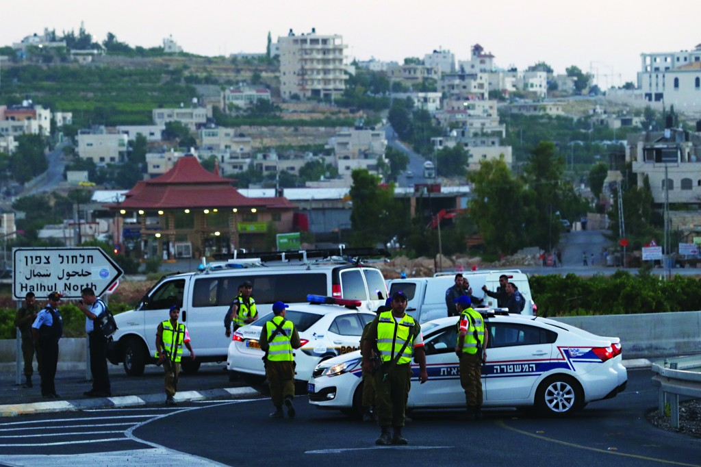 """Israeli soldiers gathered in the Palestinian village of Halhul, near Chevron, in the vicinity where the bodies of Eyal Yifrach, Naftali Frankel, and Gilad Shaar, Hy""""d, were found on Monday.  (Nati Shohat/FLASH90)"""