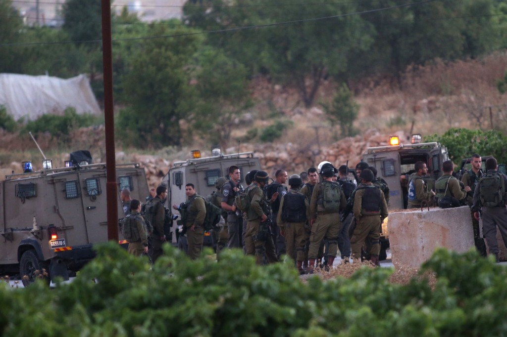 Israeli soldiers at the northern entrance to the village of Halhoul, north of Chevron, Monday, where the bodies of the three boys were discovered  (EPA/JIM HOLLANDER)