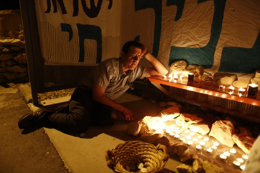 "Candles lit on Monday night at the the hitchhiking post in Gush Etzion where Eyal Yifrach, Naftali Frankel and Gilad Shaar, Hy""d, were abducted.  (Yonatan Sindel/FLASH90)"