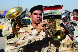 Iraqi army soldiers play music during a recruiting drive for men to volunteer for military service in Baghdad, Iraq, Tuesday. (AP Photo/Karim Kadim)