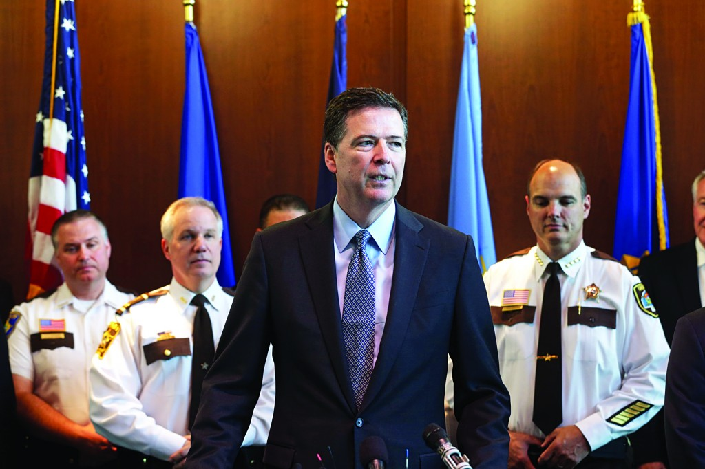 FBI Director James Comey, backed by law enforcement personnel, addresses a news conference Tuesday at the FBI Minneapolis field office in Brooklyn Center, Minn. (AP Photo/Jim Mone)