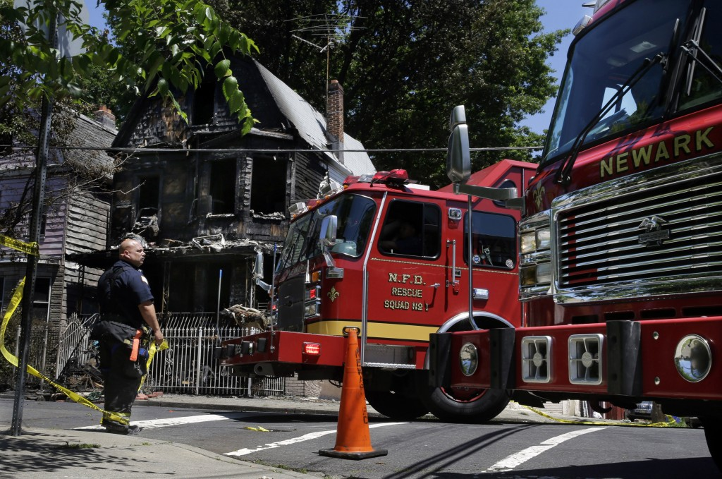 Firefighters on Sunday work near the rubble of a burned out home as they look for clues to a fire that killed six people. (AP Photo/Mel Evans)