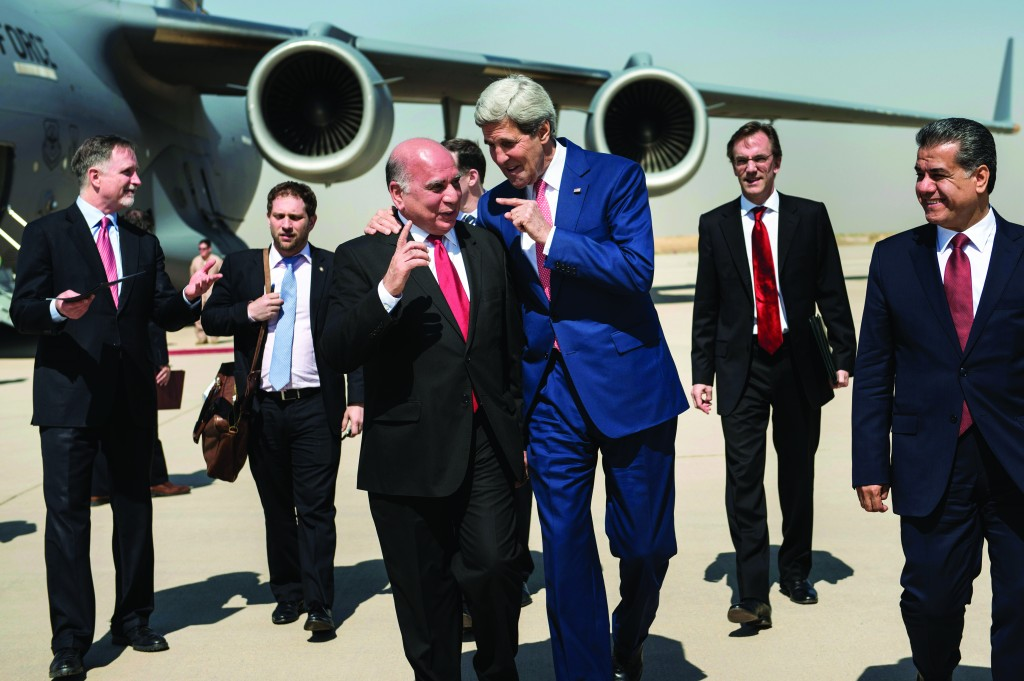 Secretary of State John Kerry, center, talks with Fuad Hussein, chief of staff for the Kurdish president, after he landed Tuesday at Irbil International Airport. (AP Photo/Brendan Smialowski)