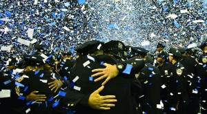 New NYPD officers embrace Monday as confetti rains down after a Police Academy graduation ceremony attended by Mayor Bill de Blasio and Commissioner William Bratton. (AP Photo/Bebeto Matthews )