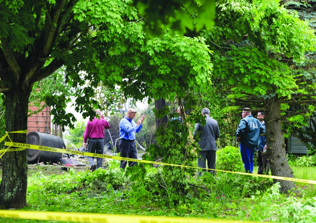 """Investigators on Tuesday rope off the site of the small airplane crash that killed Chanan Shoshany, z""""l, in East Patchogue, N.Y. (AP Photo/Kathy Kmonicek)"""