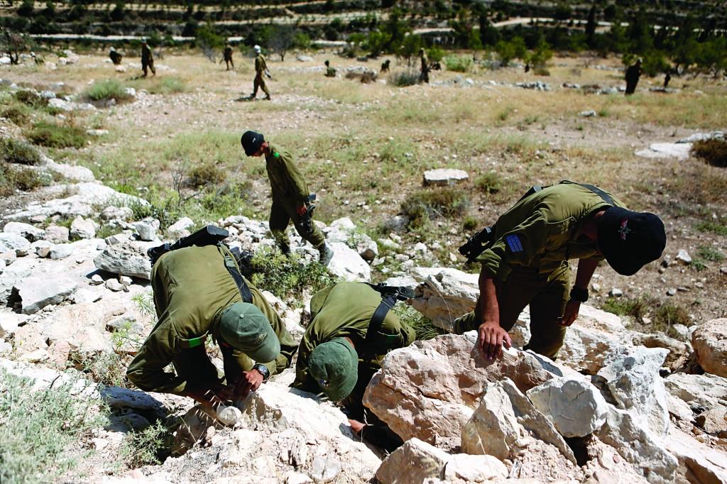 Israeli soldiers searching in fields near the Palestinian village of Halhoul, near Chevron.  (Miriam Alster/Flash90)