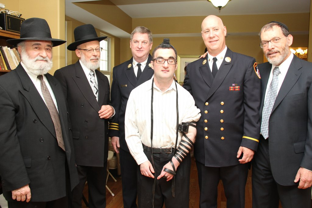 """R-L: Mr. Shmuel Kahn, executive director of HASC (Hebrew Academy for Special Children); Chief Michael Gala Jr. of the Fire Department of New York; James Leonard, deputy assistant to Chief Gala; Mr. Shalom Hurwitz, the HASC resident whose tefillin were found; Mr. Yaakov Grunfeld, who contacted Inyan Magazine's """"Lost & Found"""" column and returned the tefillin after 25 years of searching for their owner; and Mr. Shmuel Hurwitz, Shalom's father. See story on page 4. (Shimon Gifter)"""