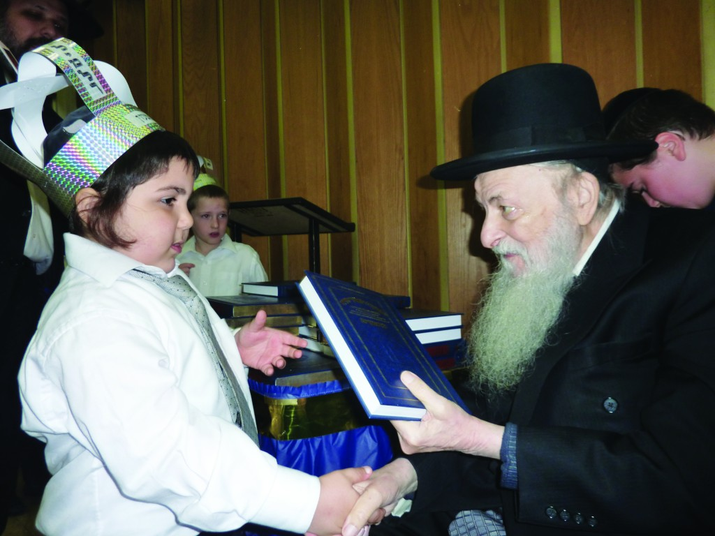 At a Chumash seudah on Sunday, Harav Moshe Feigelstock, Rosh Yeshivah of Yeshivah Tiferes Elimelech in Boro Park, gives a boy his first Chumash.