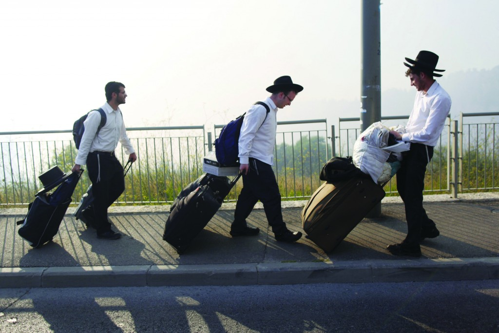 Bachurim seen carrying luggage as they evacuate their home due to a large fire raging near Yerushalayim's Ein Kerem neighborhood, Wednesday. (Yonatan Sindel/FLASH90)