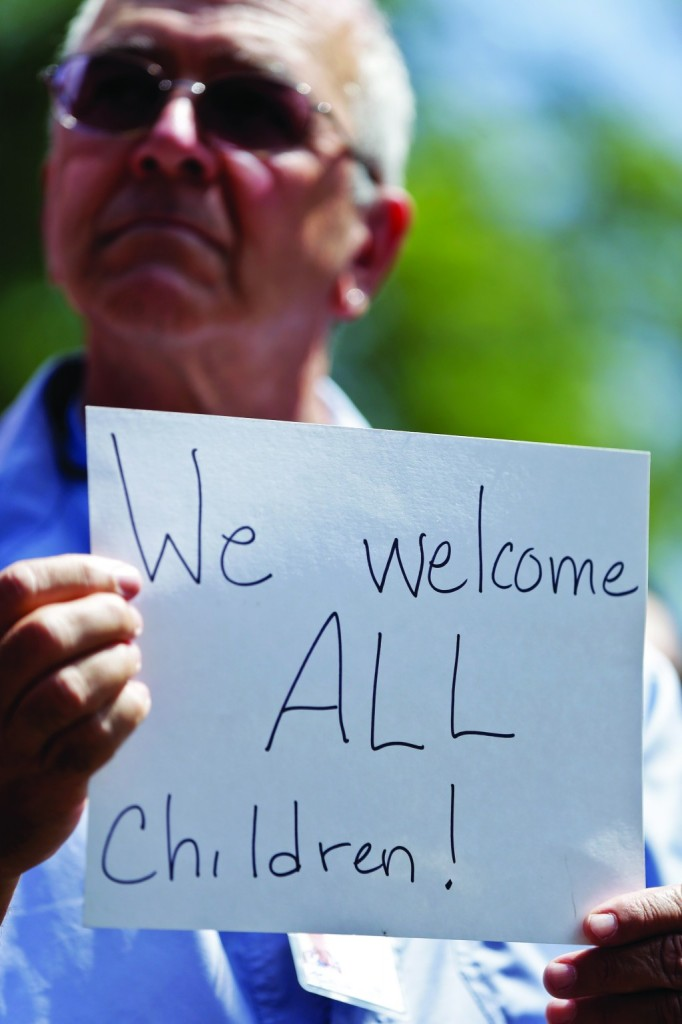 Ron Kohl holds up a sign during a rally in support of immigrants, in San Diego.  (AP Photo/Gregory Bull)