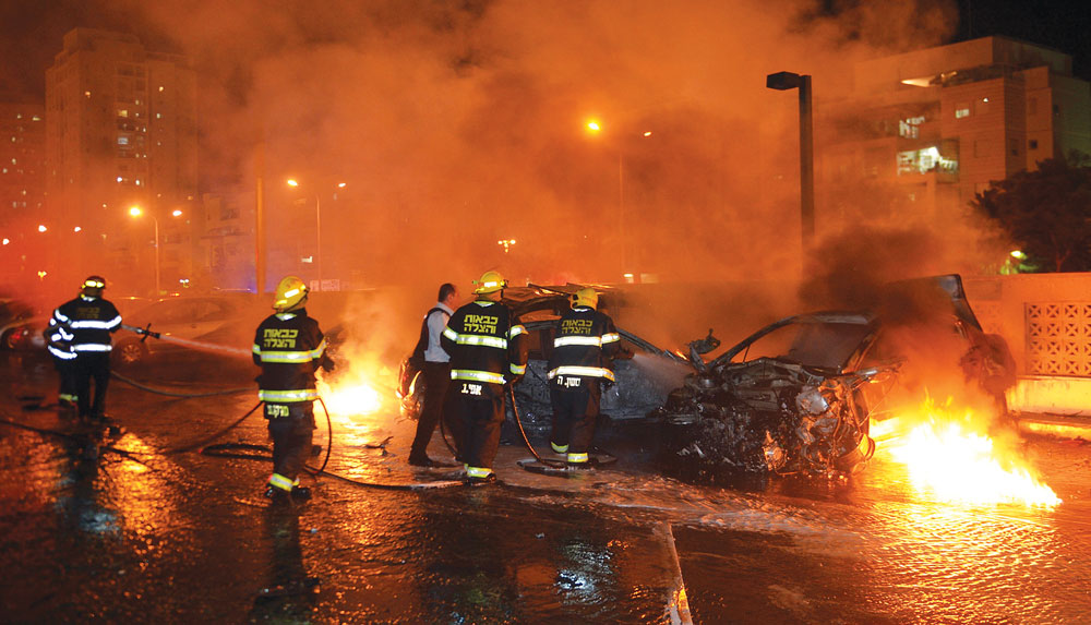 Israeli firefighters work to extinguish burning cars in a parking lot, hit by what police say was a rocket fired from Gaza in Ashdod, July 10. (REUTERS/ Avi Rokach )