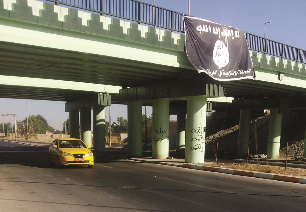 A motorist passes by a flag of the Islamic State group at the entrance of the northern Iraqi city of Mosul, Monday (AP Photo)