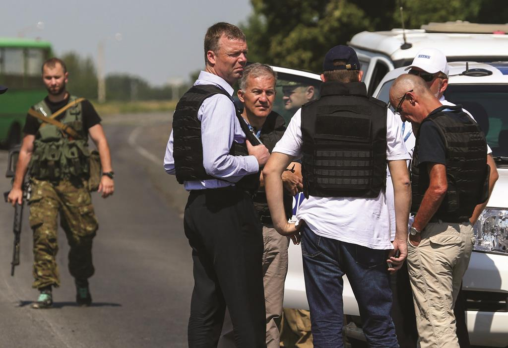 Alexander Hug (front C), deputy head for the Organization for Security and Cooperation in Europe's (OSCE) monitoring mission in Ukraine, stands with members of his team on the way to the site in eastern Ukraine where the downed Malaysian airliner MH17 crashed, outside Donetsk Wednesday (REUTERS/Sergei Karpukhin)