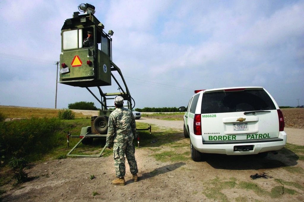 A member of the National Guard checks on his colleague inside a Border Patrol Skybox near the Hidalgo International Bridge in Hidalgo, Texas.  (AP Photo/Delcia Lopez, File)
