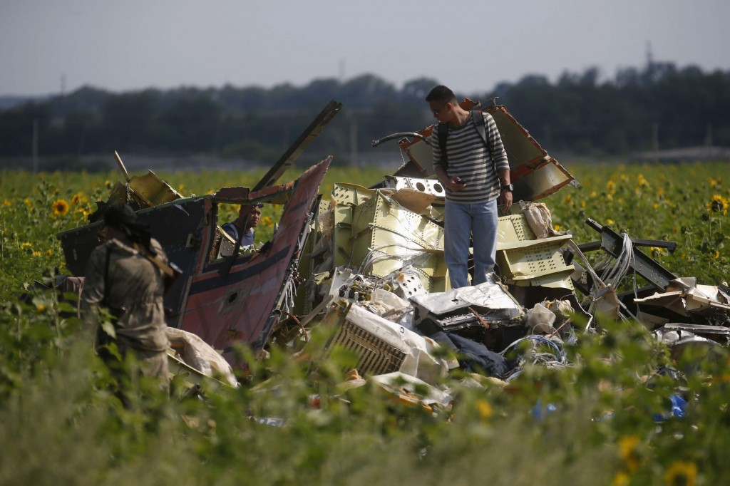 A Malaysian air crash investigator (R) inspects the crash site of Malaysia Airlines Flight MH17, near the village of Rozsypne, Donetsk region, Tuesday. (REUTERS/Maxim Zmeyev)