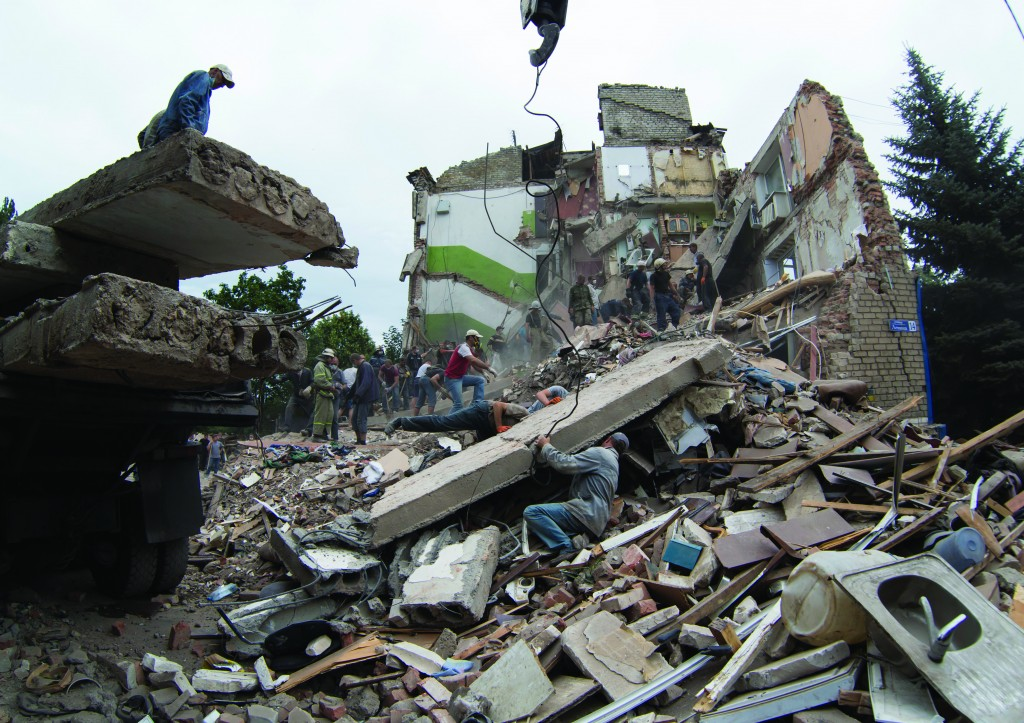 Rescue workers remove debris at a collapsed apartment after an airstrike in Snizhne, Tuesday. (AP Photo/Dmitry Lovetsky)