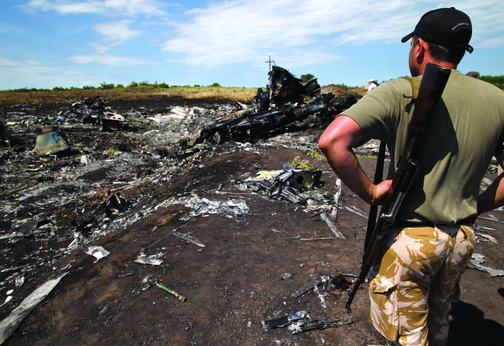 An armed man looks at charred debris at the crash site of Malaysia Airlines Flight 17 near the village of Hrabove, eastern Ukraine, Sunday (AP Photo/Vadim Ghirda)