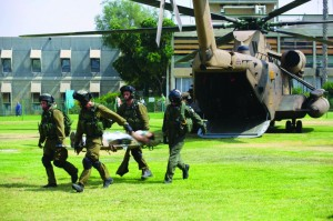 Israeli soldiers transporting a wounded soldier from a military helicopter at Soroka Hospital in Beersheba , July 21. (EPA/ABIR SULTAN)