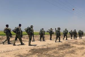 Israeli infantry troops walk into southern Israel after fighting inside the Gaza Strip, July 30.  (EPA/JIM HOLLANDER)