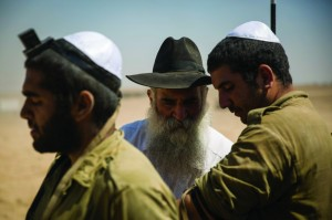 A Chabad shaliach puts tefillin on a soldier in an IDF staging area near the border with Gaza. (Hadas Parush/FLASH90)