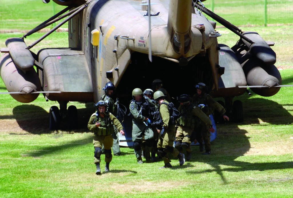 Soldiers wounded in combat in Gaza are led to the emergency room at Soroka Hospital in Be'er Sheva, after being evacuated from the field by helicopter on Friday.  (Flash90)
