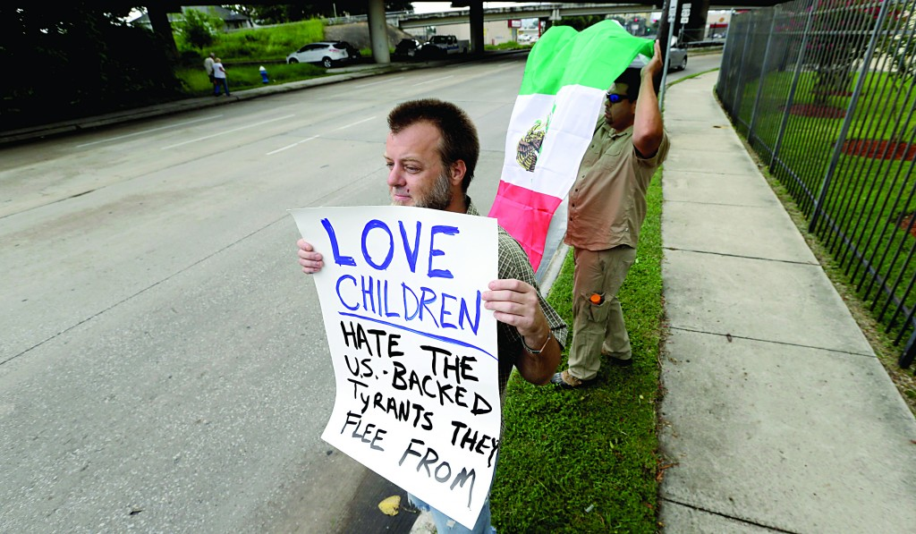 Bill Lambert holds a sign as he joins demonstrators outside the Mexican Consulate on Friday, in Houston. The sharp contrast in how Americans are reacting to the immigrant influx mirrors the divisiveness seen in Congress as the nation's leaders attempt to find solutions to an issue that could worsen in the coming months.  (AP Photo/David J. Phillip)