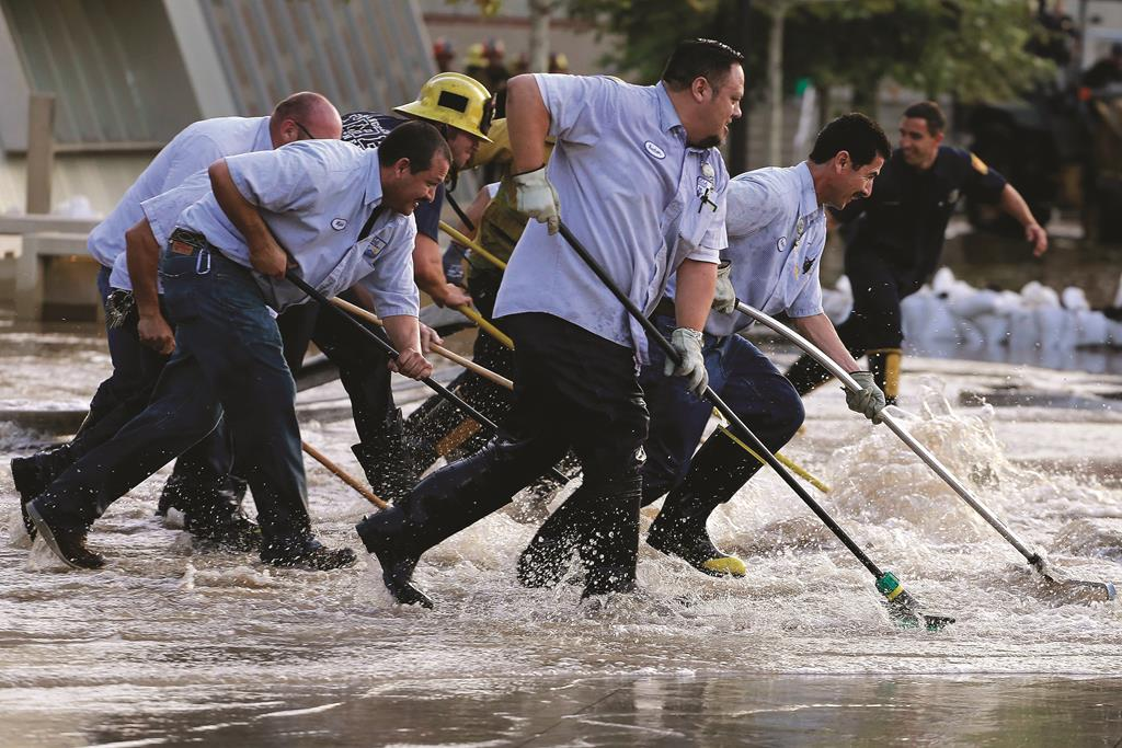 Workers push water on the UCLA campus, which was flooded by a broken thirty inch water main in the Westwood section of Los Angeles Tuesday.  (REUTERS/Jonathan Alcorn)