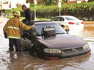 A Los Angeles firefighter helps a driver whose car became stranded on Sunset Boulevard. (AP Photo/Steve Gentry)