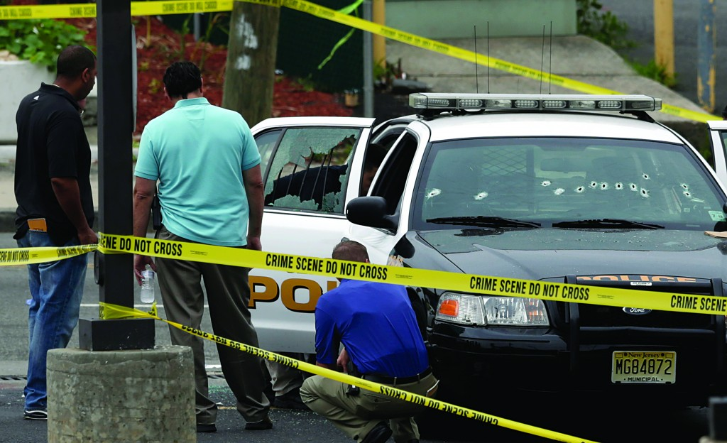 Officials investigate a Jersey City Police Department cruiser at the scene where an officer was shot and killed while responding to a call at a 24-hour pharmacy, on Sunday. (AP Photo/Julio Cortez)