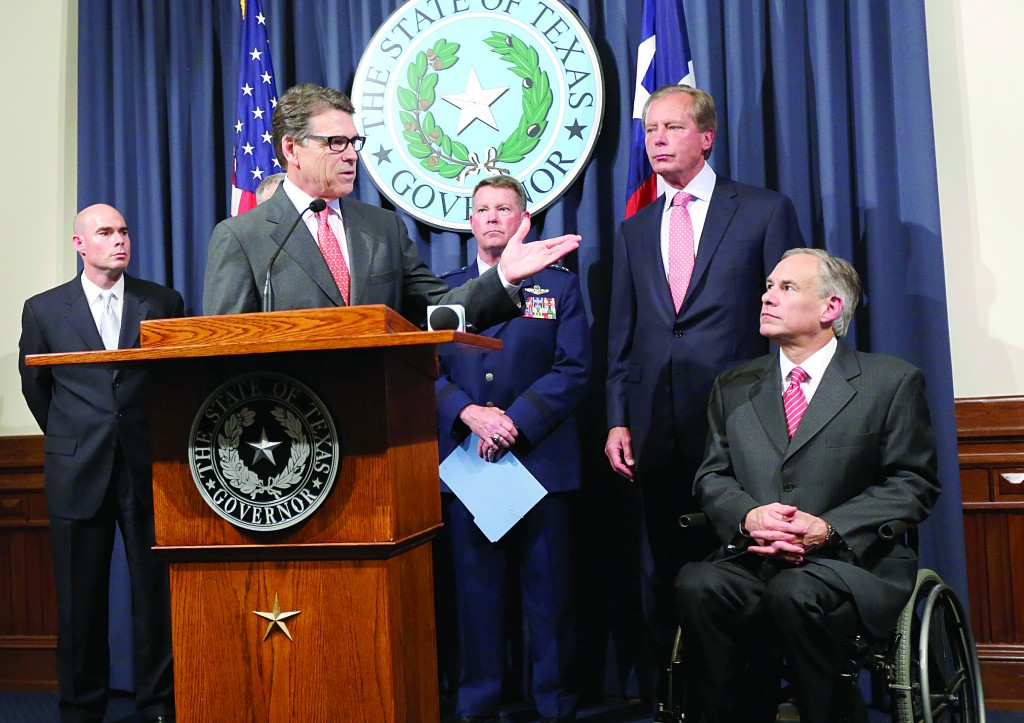 Attorney General Greg Abbott (R) listens as Gov. Rick Perry, at podium, speaks during a news conference in the Governor's press room, Monday, in Austin, Texas.  (AP Photo/Eric Gay)