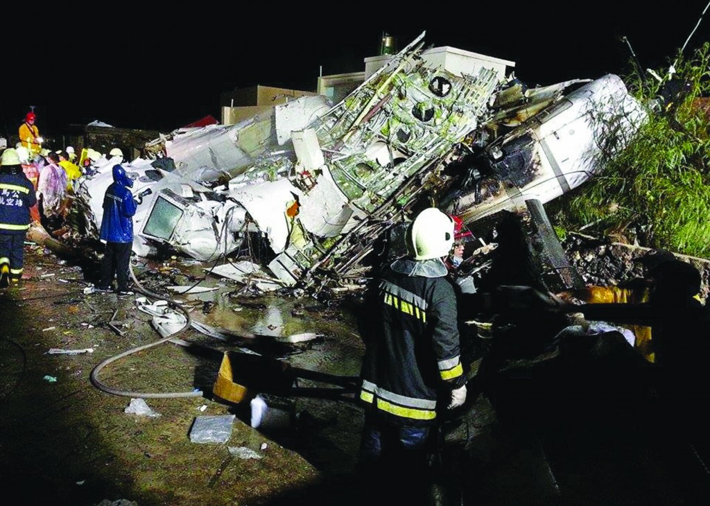 Rescue workers survey the wreckage of TransAsia Airways flight GE222, which crashed while attempting to land in stormy weather on the Taiwanese island of Penghu, late Wednesday. (AP Photo/Wong Yao-wen)