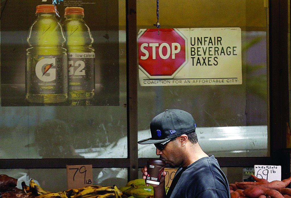 A man drinks out of a coffee cup as he walks under a sign opposed to taxes on sugary drinks posted in the window of Casa Thai Market in San Francisco. (AP Photo/Jeff Chiu)