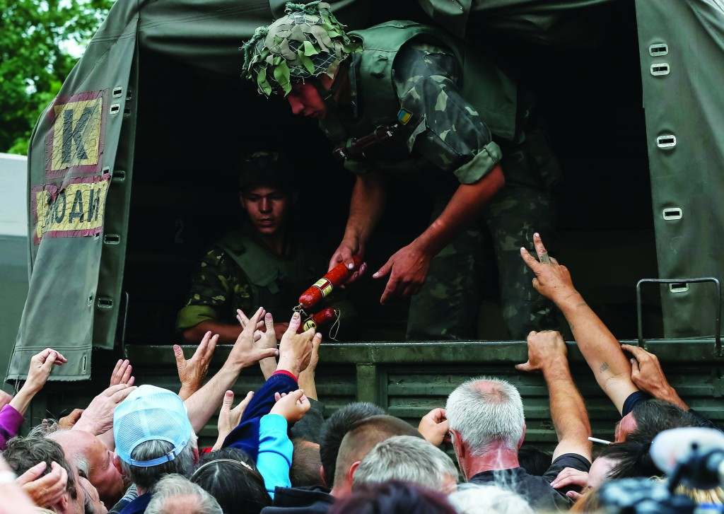 People receive food aid from Ukrainian soldiers in Slaviansk Sunday. (REUTERS/Gleb Garanich)