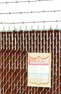 A worn and faded sign on a fence outside at the Border Patrol station in Harlingen, Texas.  (AP Photo/Valley Morning Star, David Pike)