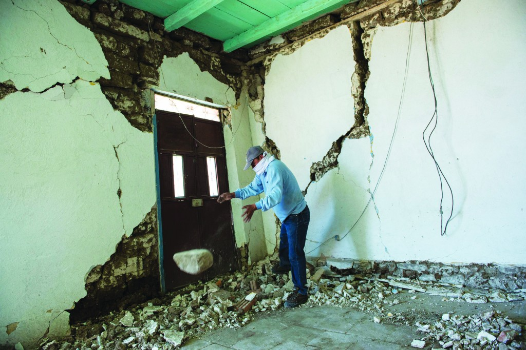 Mynor Fuentes checks his home after it was damaged during an earthquake in San Pedro, Guatemala, Monday. (AP Photo/Oliver de Ros)