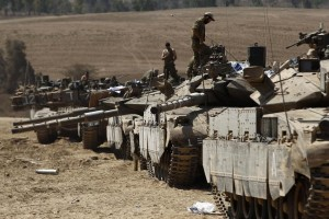 Israeli soldiers atop tanks at a staging area near the border with the Gaza Strip Thursday.  (REUTERS/Siegfried Modola)