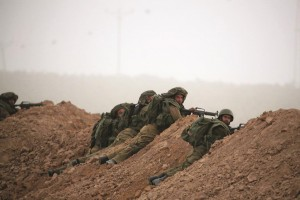 Israeli soldiers take positions near Kibbutz Nahal Oz, outside the northern Gaza Strip, during a gun battle Monday. Palestinian terrorists infiltrated into an Israeli village from the Gaza Strip and fought a gun battle with troops on Monday as an unofficial truce called for the Muslim Eid al-Fitr festival disintegrated. (REUTERS/Baz Ratner)