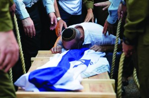 "A relative of Israeli soldier Jordan Ben-Simon, Hy""d, mourns over his coffin during his levayah in Ashkelon, Tuesday, July 22. Ben-Simon was killed while fighting in the Gaza Strip.  (AP Photo/Tsafrir Abayov)"