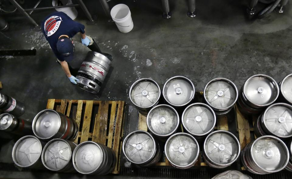 In this July 1, 2013 file photo, brewer Ken Hermann rolls a fresh keg of beer onto pallets at the Harpoon Brewery in the Seaport District of Boston.  (AP Photo/Charles Krupa, File)