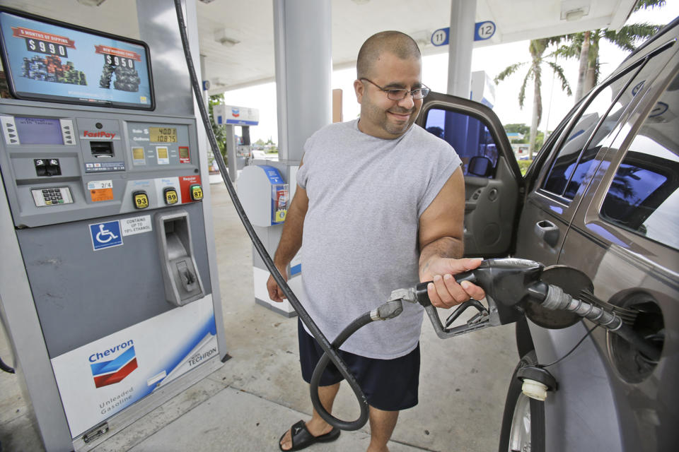 In this Wednesday, June 4, 2014 photo, Baltazar Rosado, of Hollywood, Fla., pumps gasoline into his car at a Chevron gasoline station in Pembroke Pines, Fla. The Labor Department reported on U.S. consumer prices in June on Tuesday, July 22, 2014. (AP Photo/Wilfredo Lee)