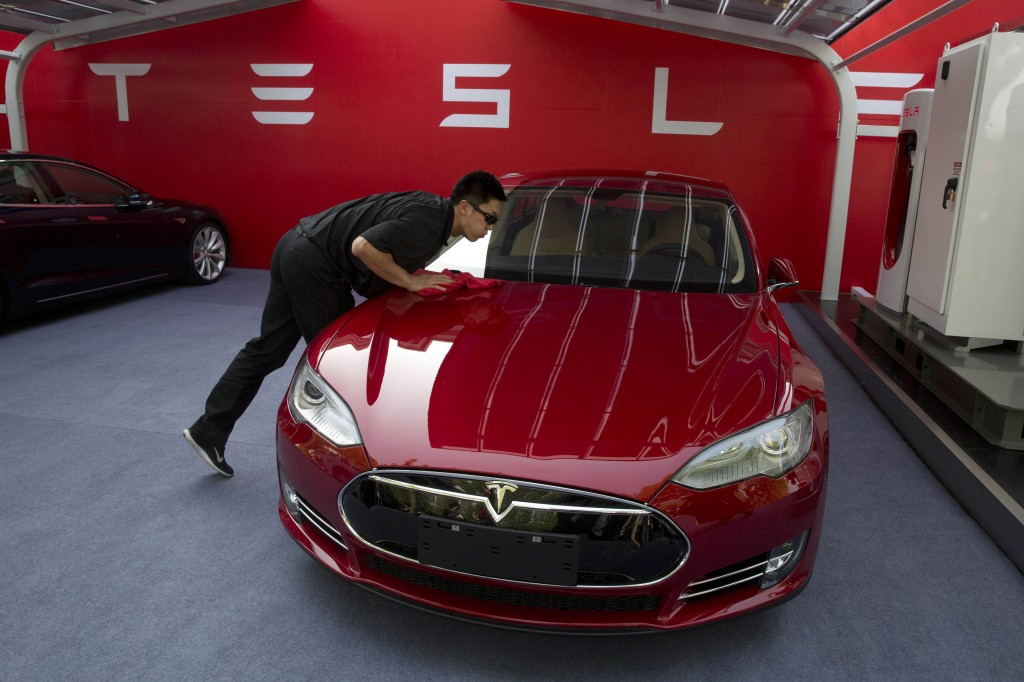In this April 22, 2014 file photo, a worker cleans a Tesla Model S sedan before an event to deliver the first set of cars to customers in Beijing. (AP Photo/Ng Han Guan, File)